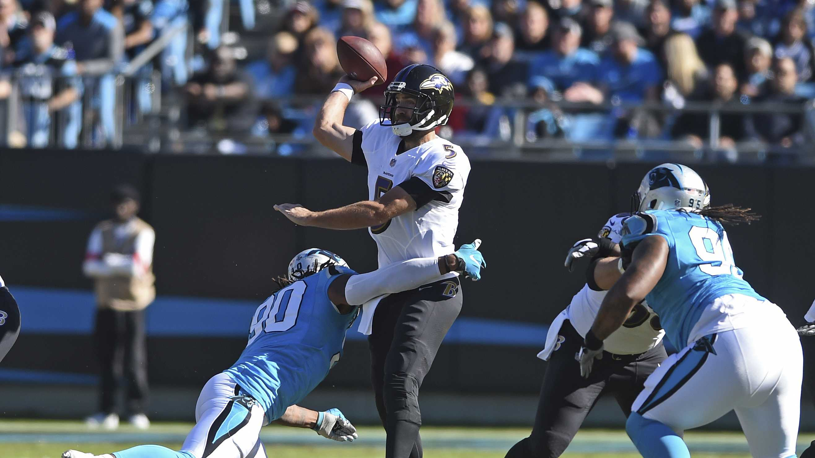 Baltimore Ravens' Joe Flacco (5) throws a pass under pressure from Carolina Panthers' Julius Peppers (90) in the second half of an NFL football game in Charlotte, N.C., Sunday, Oct. 28, 2018. (AP Photo/Mike McCarn)