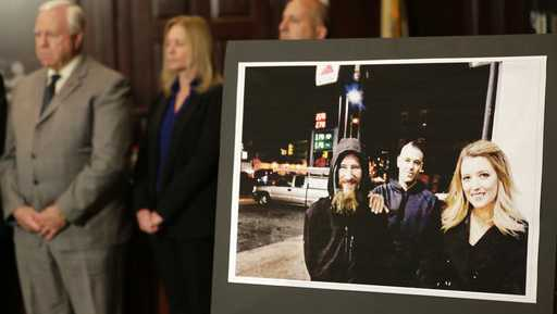 "A picture of Katelyn McClure, right, Mark D'Amico, center, and Johnny Bobbitt Jr. is displayed during a news conference in Mt. Holly, N.J., Thursday, Nov. 15, 2018. Authorities say a New Jersey couple and a homeless man, Bobbitt Jr., made up a ""feel good"" story about the man helping them so they could raise money through an online fundraiser."