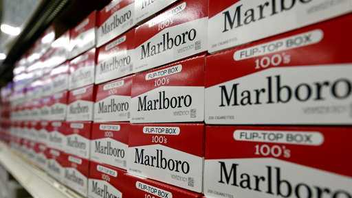 FILE- This June 14, 2018, file photo shows cartons of Marlboro cigarettes on the shelves at JR outlet in Burlington, N.C. Curiosity from one the world's largest tobacco companies about the marijuana business sent shares of a Canadian cannabis company higher at the opening bell Tuesday, Dec. 4. Cronos Group confirmed talks late Monday with Marlboro maker Altria about a possible investment.
