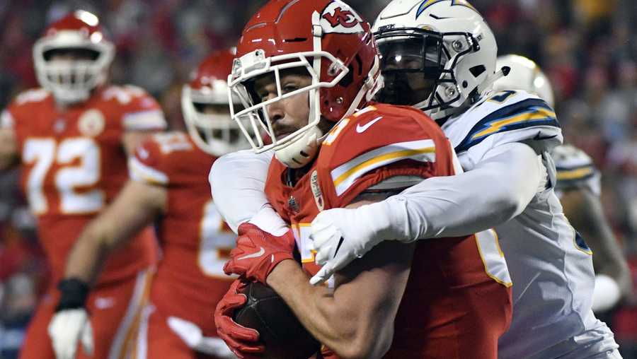Kansas City Chiefs tight end Travis Kelce (87) is tackled by Los Angeles Chargers linebacker Jatavis Brown (57) during the first half of an NFL football game in Kansas City, Mo., Thursday, Dec. 13, 2018. (AP Photo/Ed Zurga)