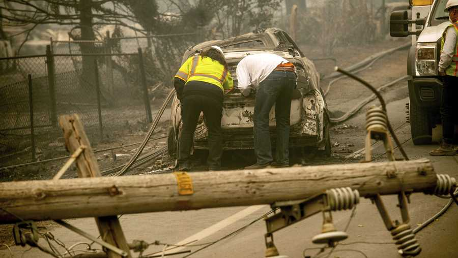 FILE - In this Nov. 10, 2018 file photo, with a downed power utility pole in the foreground, Eric England, right, searches through a friend's vehicle after the wildfire burned through Paradise, Calif. Pacific Gas & Electric Corp. is expected to file for bankruptcy protection Tuesday, Jan. 29, 2019. (AP Photo/Noah Berger, File)