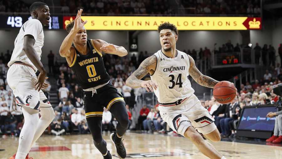 Cincinnati's Jarron Cumberland (34) drives past Wichita State's Dexter Dennis (0) in the second half of an NCAA college basketball game, Sunday, Feb. 17, 2019, in Cincinnati. (AP Photo/John Minchillo)