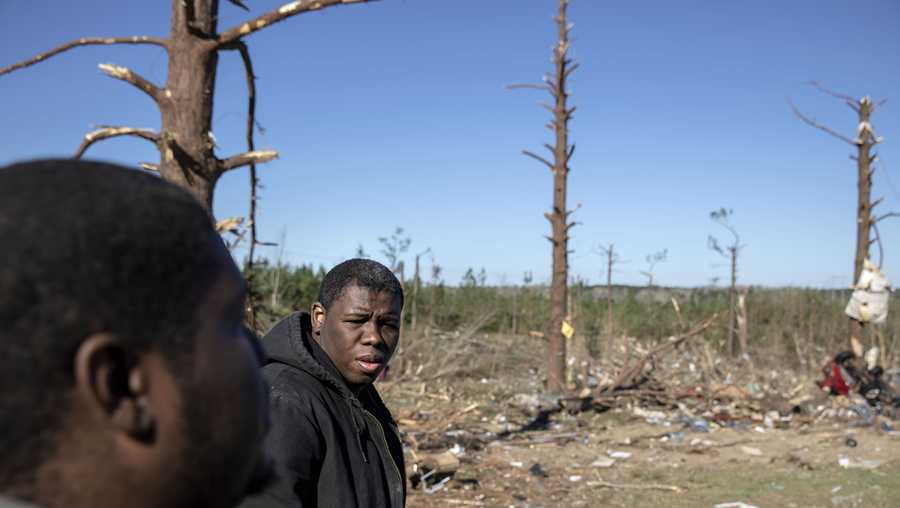 Demetria Jones, right, and his cousin Cordarrly Jones, walk through the damaged neighborhood where they said they lost ten relatives in a tornado in Beauregard, Ala., Tuesday, March 5, 2019.