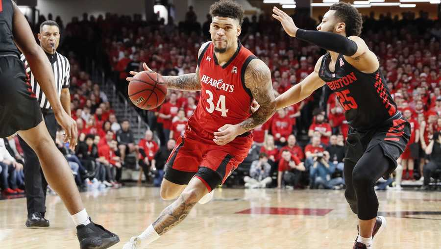 Cincinnati's Jarron Cumberland (34) drives past Houston's Galen Robinson Jr. (25) in the first half of an NCAA college basketball game, Sunday, March 10, 2019, in Cincinnati. (AP Photo/John Minchillo)