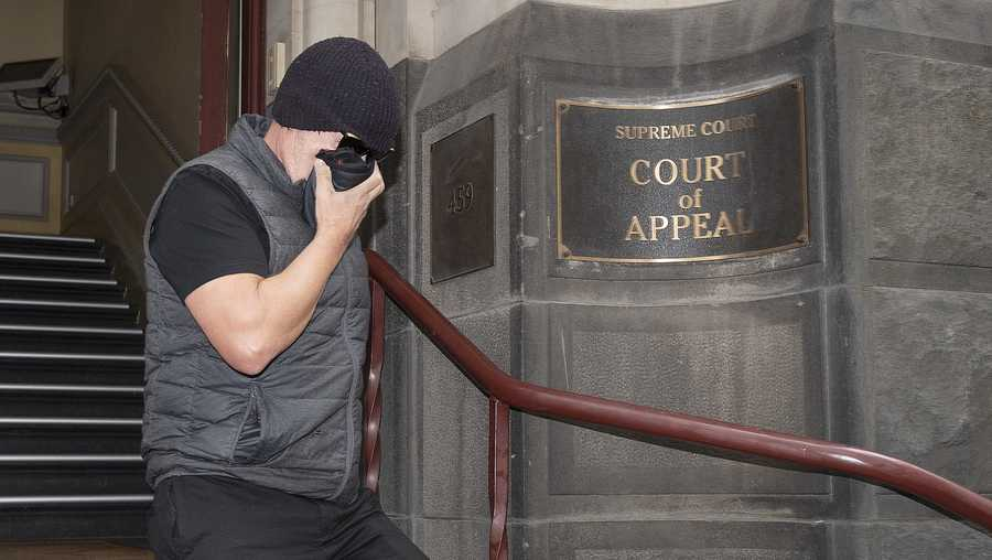 Workplace bullying claimant David Hingst covers his face as he leaves the Court of Appeal in Melbourne, Australia Friday, March 29, 2019. The Australian appeals court on Friday dismissed a bullying case brought by the engineer Hingst who accused his former supervisor of repeatedly breaking wind toward him. (Ellen Smith/AAP Image via AP)