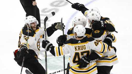 Boston Bruins left wing Jake DeBrusk (74) joins the celebration after Brandon Carlo, right, scored a goal against the St. Louis Blues during the third period of Game 6 of the NHL hockey Stanley Cup Final Sunday, June 9, 2019, in St. Louis.