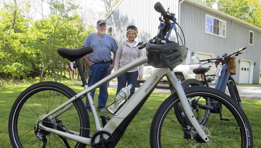 In this June 8, 2019 photo, Gordon and Janice Goodwin show their electric-assist bicycles outside their home in Bar Harbor, Maine. The bikes are banned on carriage roads and bicycle paths in nearby Acadia National Park. (AP Photo/David Sharp)