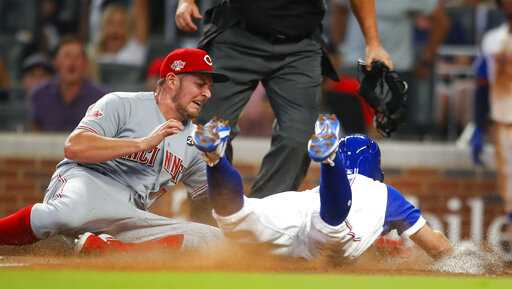 Cincinnati Reds starting pitcher Trevor Bauer, left, tags out Atlanta Braves' Ender Inciarte, right, at home in the fourth inning of a baseball game, Saturday, Aug.3, 2019, in Atlanta. (AP Photo/Todd Kirkland)
