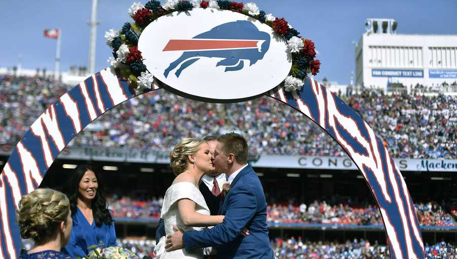 Mackenzie Park and Jordan Binggeli share a kiss after being married at midfield during halftime of an NFL football game between the Buffalo Bills and the New England Patriots, Sunday, Sept. 29, 2019, in Orchard Park, N.Y. (AP Photo/Adrian Kraus)