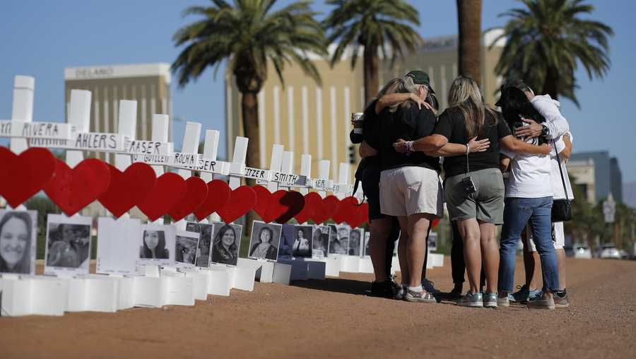 People pray at a makeshift memorial for shooting victims, Tuesday, Oct. 1, 2019, in Las Vegas, on the anniversary of the mass shooting two years earlier.