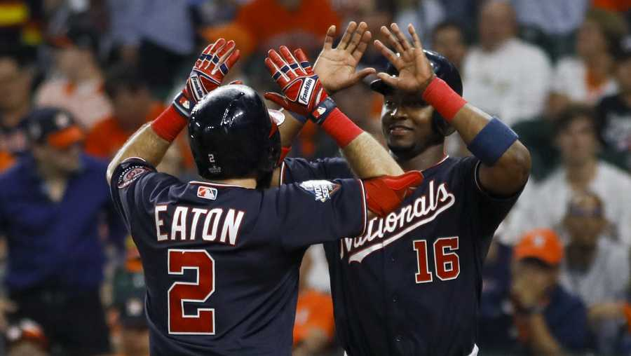 Washington Nationals' Adam Eaton celebrates his two-run home run with Victor Robles during the eighth inning of Game 2 of the baseball World Series against the Washington Nationals Wednesday, Oct. 23, 2019, in Houston. (AP Photo/Matt Slocum)