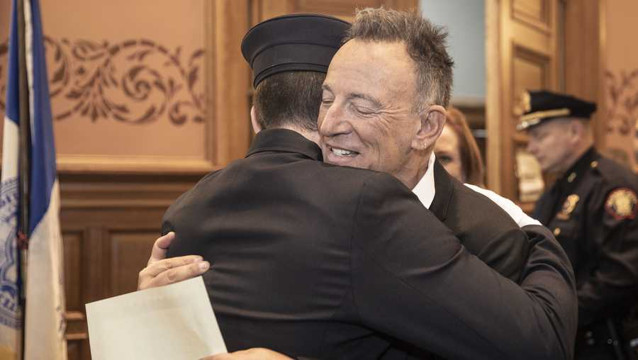 In this photo provided by the Jersey City Mayor's Office, Bruce Springsteen hugs his son Sam Springsteen after he is sworn in as a Jersey City Firefighter at City Hall in Jersey City, N.J. on Tuesday, Jan. 14, 2020.