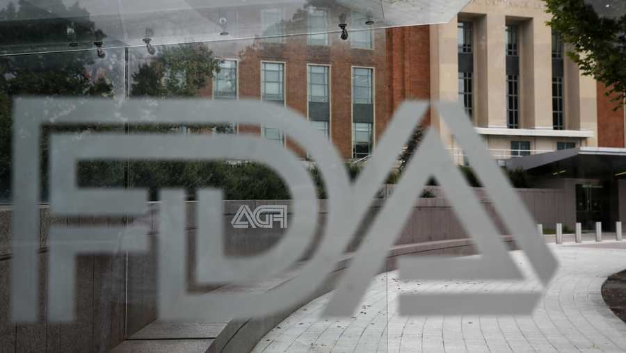 FILE - In this Aug. 2, 2018, file photo, the U.S. Food and Drug Administration (FDA) building is visible behind FDA logos at a bus stop on the agency's campus in Silver Spring, Md. The U.S. Food and Drug Administration has for the first time approved a video game for treating attention deficit hyperactivity disorder in children. The FDA said Monday, June 15, 2020, the game built by Boston-based Akili Interactive Labs can improve attention function. (AP Photo/Jacquelyn Martin, File)