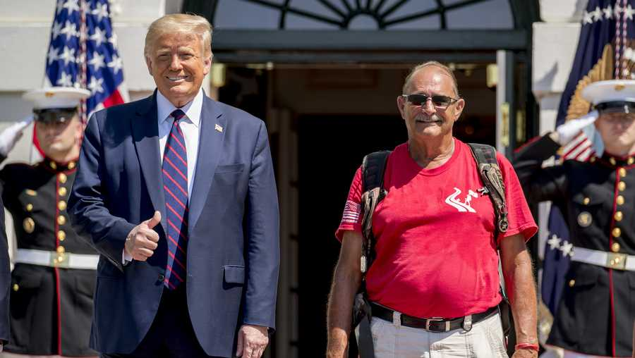"President Donald Trump gives a thumbs up as he poses for photographs with Terry Sharpe, right, known as the ""Walking Marine"" as he arrives at the White House in Washington, Monday, July 27, 2020. Sharpe has walked from Summerfield, N.C., to Washington to raise awareness of the current veteran suicide rate. (AP Photo/Andrew Harnik)"