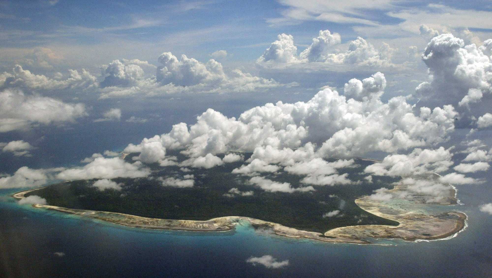 In this Nov. 14, 2005 file photo, clouds hang over the North Sentinel Island, in India's southeastern Andaman and Nicobar Islands. India used heat sensors on flights over hundreds of uninhabited Andaman Sea islands Friday, March 14, 2014, and will expand its search for the missing Malaysia Airlines jet farther west into the Bay of Bengal, officials said. The Indian-controlled archipelago that stretches south of Myanmar contains 572 islands covering an area of 720-by-52 kilometers. Only 37 are inhabited, with the rest covered in dense forests.