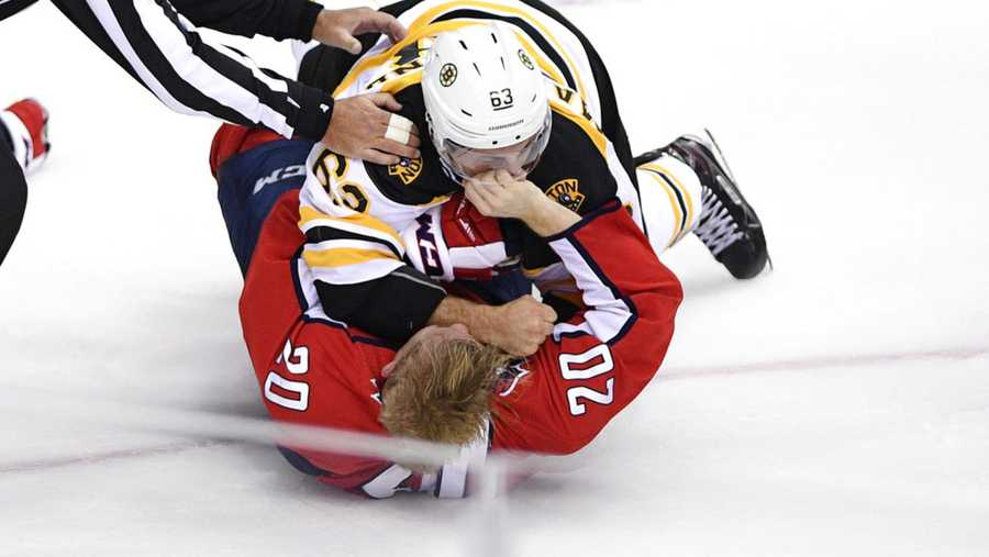 Boston Bruins left wing Brad Marchand (63) fights with Washington Capitals center Lars Eller (20), of Denmark, during the third period of an NHL hockey game Wednesday, Oct. 3, 2018, in Washington. The Capitals won 7-0. (AP Photo/Nick Wass)