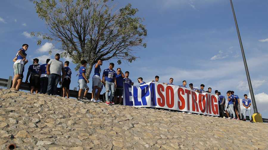 "Members of the Americas High School football team from El Paso carry an ""El Paso Strong"" sign into place near the site of a mass shooting over the weekend at a shopping complex, Monday, Aug. 5, 2019, in El Paso, Texas. (AP Photo/John Locher)"