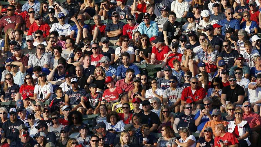 Fans in the bleachers at Fenway Park during the first inning of a baseball game between the Boston Red Sox and the Los Angeles Dodgers in Boston, Saturday, July 13, 2019. (AP Photo/Michael Dwyer)