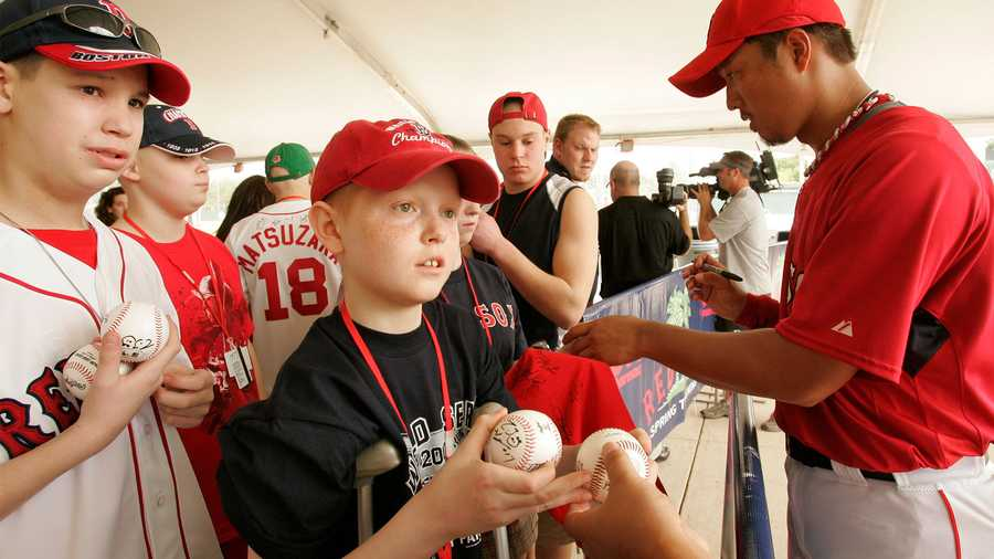 In this March 4, 2008 file photo, Victor Naeve, center, of Dedham, Mass., a 13-year-old cancer patient, stands on crutches as he prepares to receive an autograph from Boston Red Sox pitcher Hideki Okajima, right, at a signing event before a spring training baseball game at City of Palms Park in Fort Myers, Fla. Naeve was among 32 young cancer patients from Massachusetts who were able to visit spring training due to public contributions and the Jimmy Fund. (AP Photo/Steven Senne)