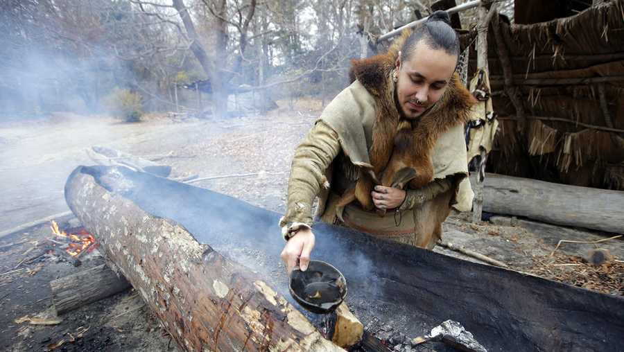 In this Thursday, Nov. 15, 2018, photo, Mashpee Wampanoag Phillip Wynne, of Sagamore, Mass., pours water to control fire and temperatures while making a mishoon, a type of boat, from a tree at the Wampanoag Homesite at Plimoth Plantation, in Plymouth, Mass. Plymouth, where the Pilgrims came ashore in 1620, is gearing up for a 400th birthday, and everyone's invited, especially the native people whose ancestors wound up losing their land and their lives. (AP Photo/Steven Senne)