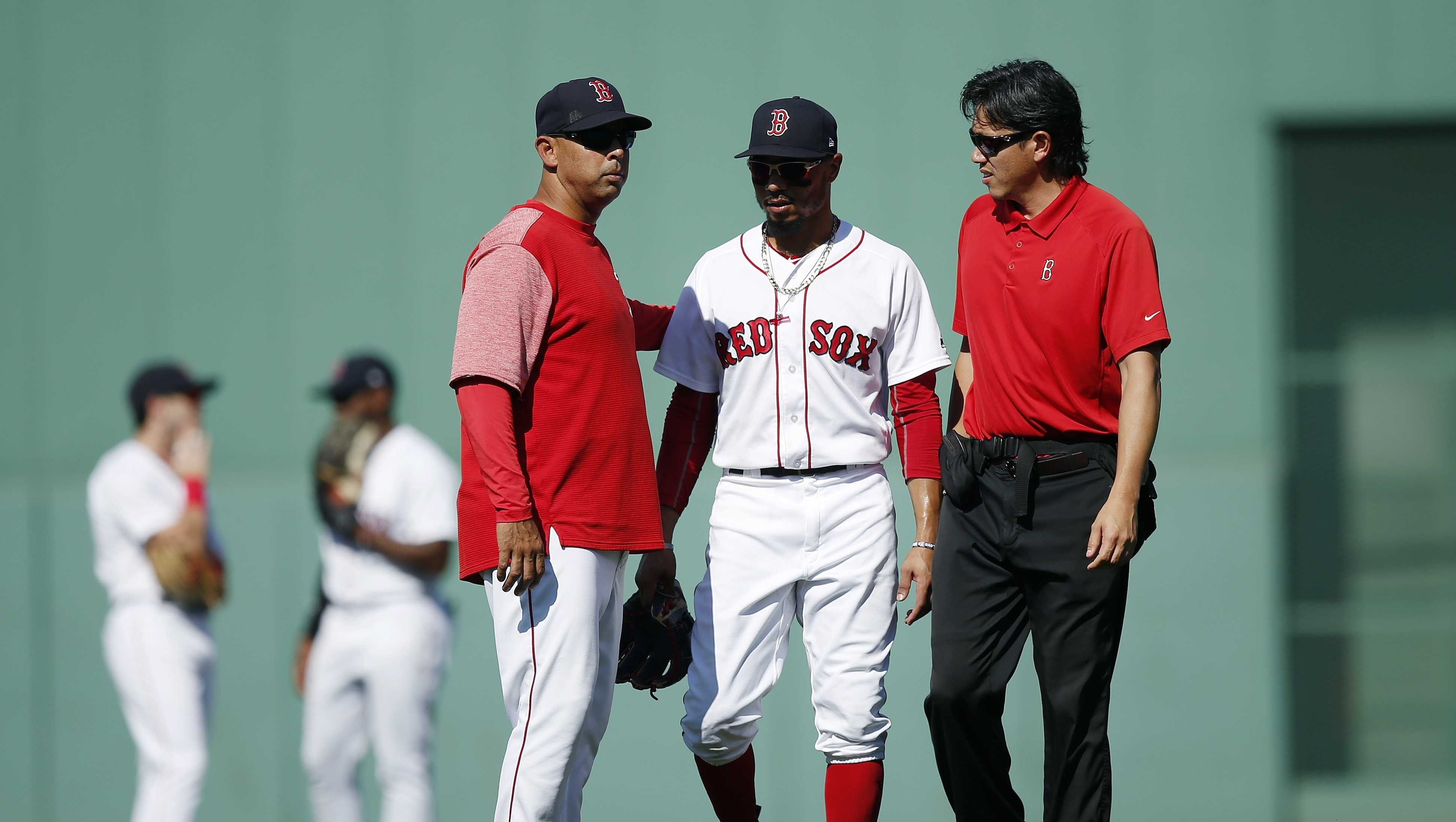 Boston Red Sox manager Alex Cora, foreground left, escorts Mookie Betts, center, off the field during the sixth inning of a baseball game against the New York Mets in Boston, Sunday, Sept. 16, 2018. (AP Photo/Michael Dwyer)