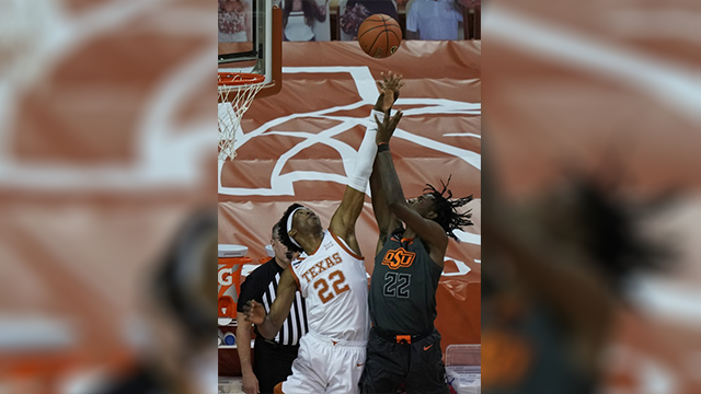 Texas' Kai Jones, left, blocks a shot by Oklahoma State's Kalib Boone, right, during the first half of an NCAA college basketball game in Austin, Texas, Sunday, Dec. 20, 2020. (AP Photo/Chuck Burton)