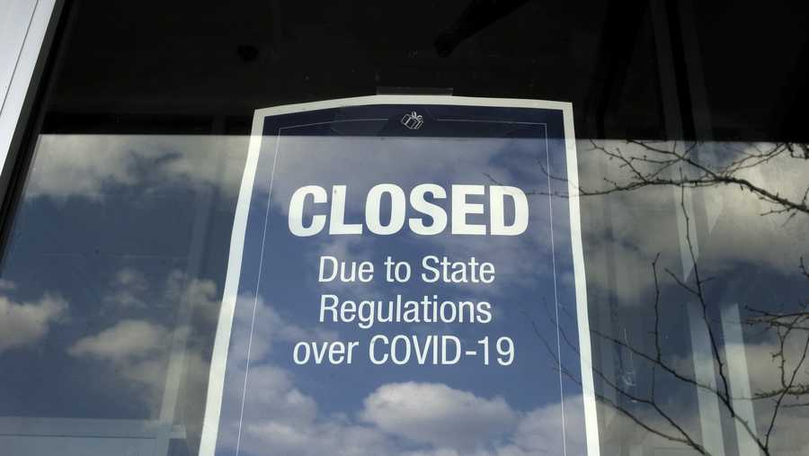 In this Wednesday, April 22, 2020 photo a closed sign is posted in the window of a store because of the coronavirus, in an outdoor mall, in Dedham, Mass.
