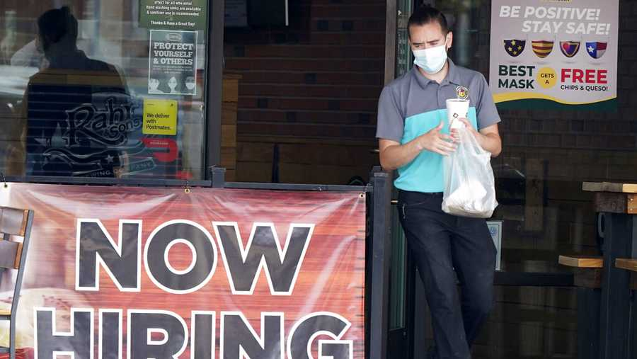 FILE - In this Sept. 2, 2020 file photo, a customer wears a face mask as they carry their order past a now hiring sign at an eatery in Richardson, Texas. (AP Photo/LM Otero, File)