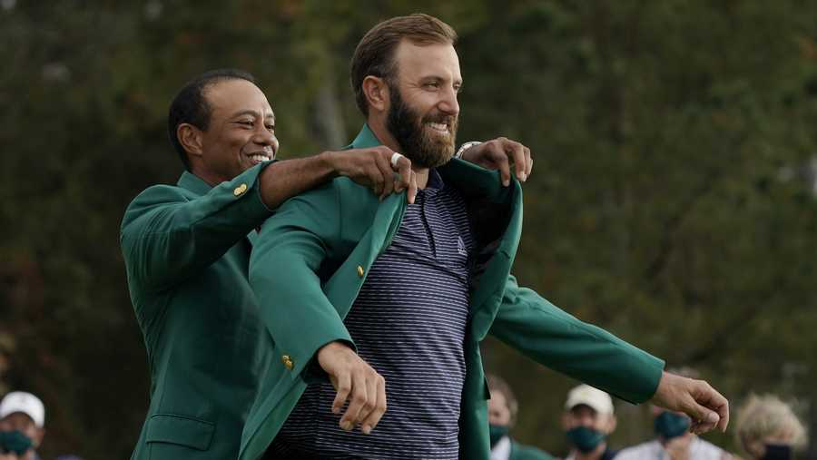 Tiger Woods helps Masters champion Dustin Johnson with his green jacket after his victory at the Masters golf tournament Sunday, Nov. 15, 2020, in Augusta, Ga.
