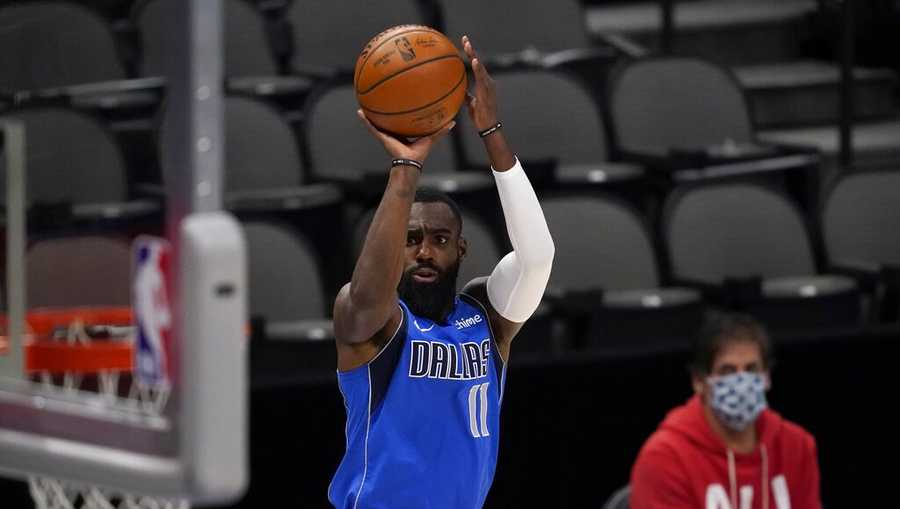 Dallas Mavericks forward Tim Hardaway Jr. (11) shoots as team owner Mark Cuban watches during the first half of the team's NBA basketball game against the Golden State Warriors in Dallas, Thursday, Feb. 4, 2021. (AP Photo/Tony Gutierrez)