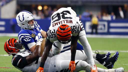 Indianapolis Colts quarterback Andrew Luck (12) is tackled by Cincinnati Bengals defensive end Michael Johnson (90) and defensive back Shawn Williams (36) during the first half of an NFL football game in Indianapolis, Sunday, Sept. 9, 2018. Williams was disqualified for his hit on Luck. (AP Photo/Jeff Roberson)