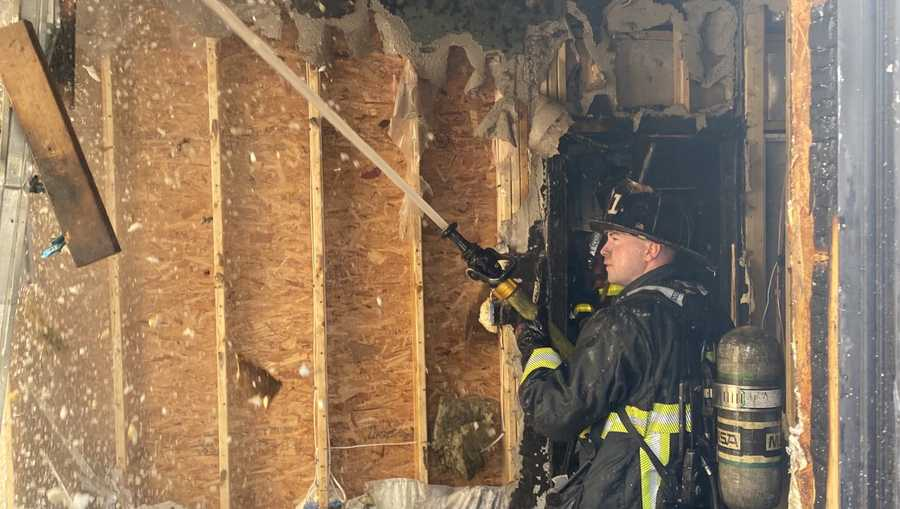 Firefighter works inside a heavily damaged home on Mansfield Street in Boston.