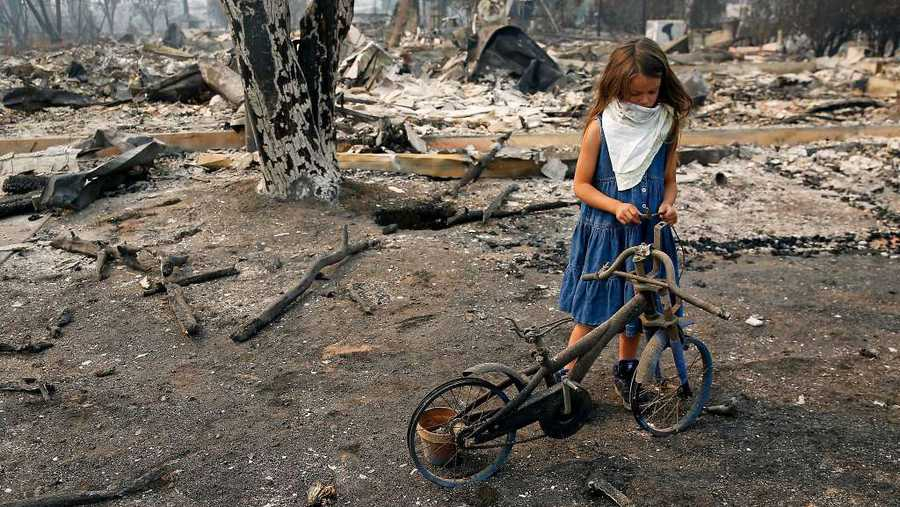 ​Arilyn Edwards, 6, stands beside her bike in front of the rubble of her Santa Rosa home​.