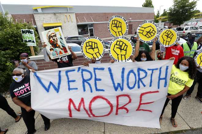 Protesters rally outside a McDonald's in Detroit, Monday, July 20, 2020. The national workers strike saw people walk off the job Monday in U.S. cities to protest systemic racism and economic inequality. (AP Photo/Paul Sancya)