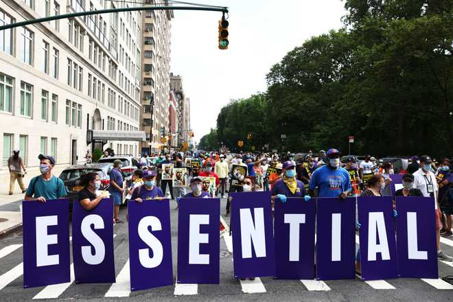 "Members of the 32BJ union hold up signs spelling out ""Essential Workers"" during a ""Strike for Black Lives"" rally on July 20, 2020 in New York City."