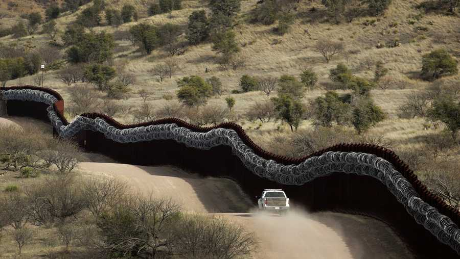 This March 2, 2019 photo shows a Customs and Border Control agent patrols on the U.S. side of a razor-wire-covered border wall along the Mexico east of Nogales, Ariz. President Joe Biden rushed to send the most ambitious overhaul of the nation's immigration system in a generation to Congress and signed nine executive actions to wipe out some of his predecessor's toughest measures to fortify the U.S.-Mexico border. But a federal court in Texas suspended his 100-day moratorium on deportations. (AP Photo/Charlie Riedel,File)