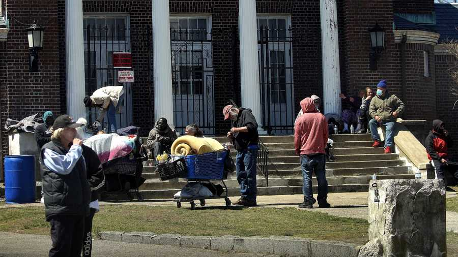 FILE PHOTO — Homeless people congregate on the steps of the former Keys Of The Kingdom Tabernacle Of Prayer building on Main street in downtown Brockton, MA on April 23, 2020. High COVID-19 rates have been reported in Brockton and Randolph.