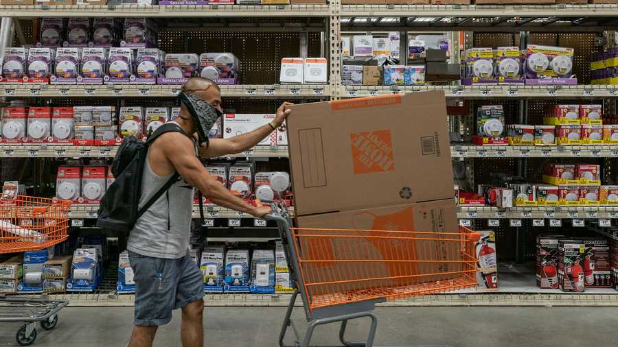 A shopper wearing a protective mask pushes a cart at a Home Depot Inc. store in Jersey City, New Jersey, U.S., on Friday, Aug. 14, 2020. Home Depot is scheduled to release earnings figures on August 18. Photographer: Jeenah Moon/Bloomberg via Getty Images