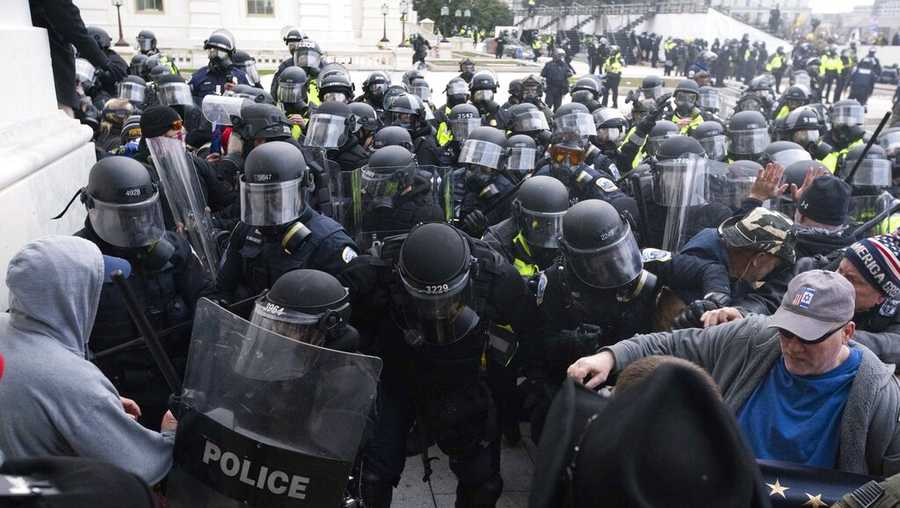 "In this Jan. 6, 2021, file photo, U.S. Capitol Police push back rioters trying to enter the U.S. Capitol in Washington. A former State Department aide in President Donald Trump's administration has been charged with participating in the deadly siege at the Capitol. Court papers say Federico Klein was seen wearing a ""Make America Great Again"" hat amid the throng of people trying to force their way into the Capitol. Authorities say Klein pushed his way toward the doors, where ""he physically and verbally engaged"" with officers trying to keep the mob back. Klein resigned from his position on Jan. 19, the day before Joe Biden was sworn in as president. (AP Photo/Jose Luis Magana, File)"