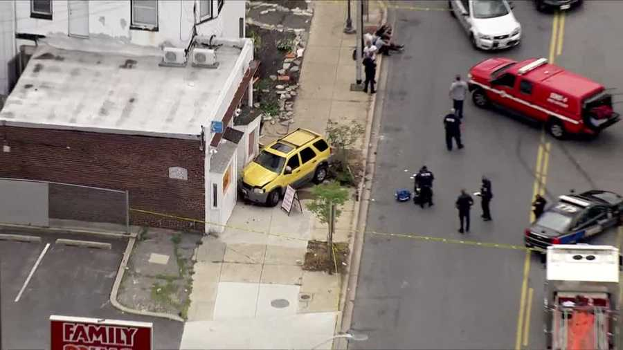 An SUV hits two people on a sidewalk and crashes into building on York Road.