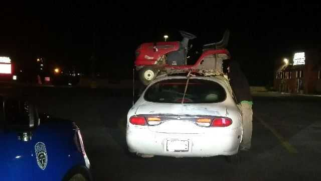 Riding lawn mower strapped to roof of car