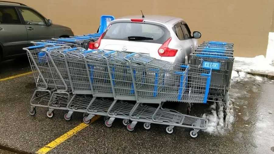 Shopping carts surround a poorly parked car in Biddeford, Maine.