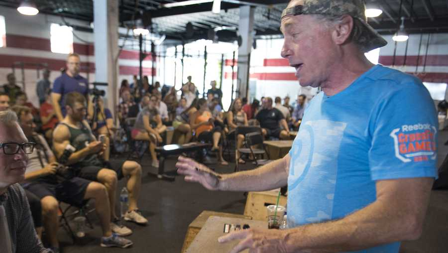 Crossfit Inc. founder and CEO Greg Glassman (R) talks to employees prior to a presentation at the Half street location in Washington, DC on July 31, 2015.