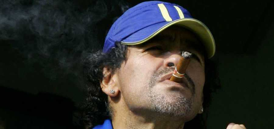 FILE - In this March 26, 2006 file photo, former soccer player Diego Maradona smokes a cigar as he watches Argentina's first division soccer match between Boca Juniors and River Plate  in Buenos Aires, Argentina.