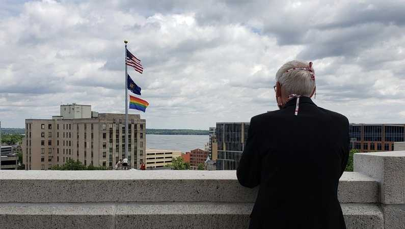 Gov. Tony Evers watches as the pride flag is raised at the Wisconsin state Capitol in Madison