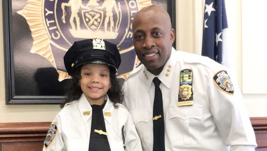 A 5-year-old girl rescued from under a subway train that killed her father became an honorary New York Police Department officer.