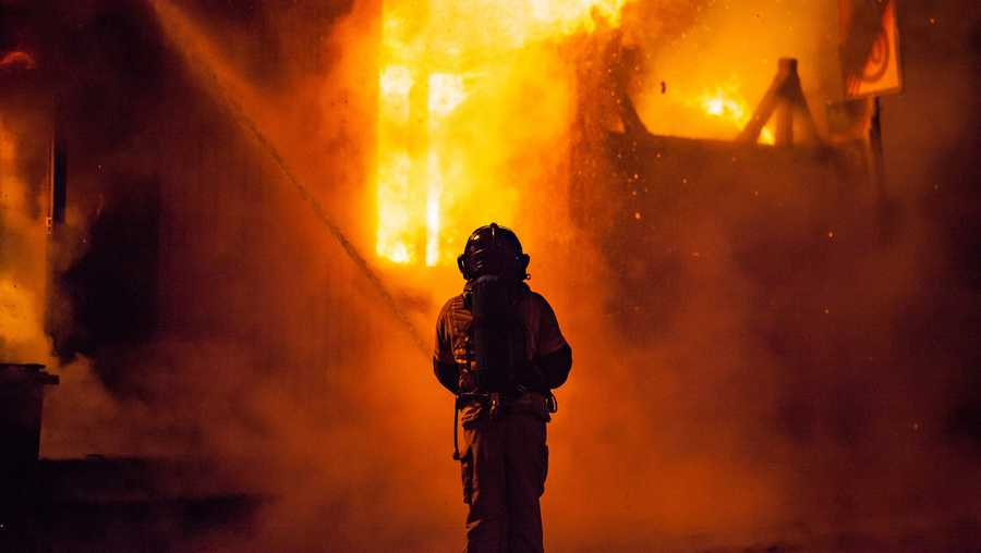A firefighter battles a blaze at night.
