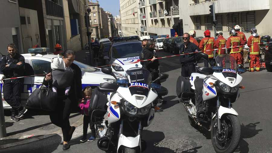 Police officers and rescue workers cordon off a street during searches in Marseille, southern France, Tuesday, April 18, 2017.