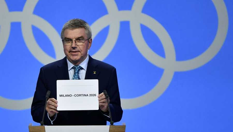 International Olympic Committee (IOC) president Thomas Bach shows the card with the name Milan/Cortina d'Ampezzo as the winning name of the 2026 Winter Olympics during the 134th session of the International Olympic Committee (IOC), in Lausanne on June 24, 2019.