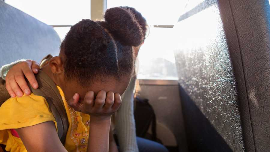 A female junior high student rubs her eyes and cries as her best friend beside her comforts her while they are riding on a school bus.